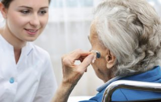 Senior woman inserts hearing aid in her ear